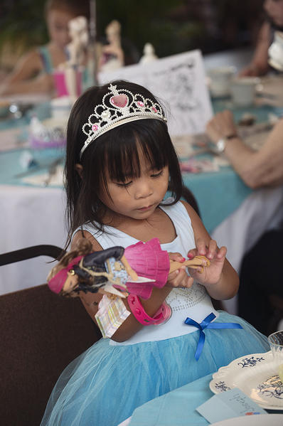 Dressed as a princess, Alexia Le, 3, from Davie, plays with a Barbie doll during a Tea with Barbie event at the Old Davie School Historical Museum.
