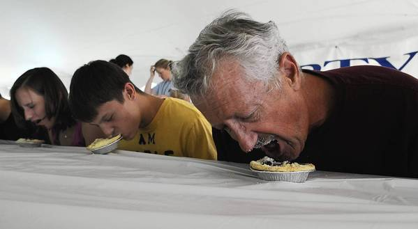 (From left to right) Ashley and Adam Kuronya of Northampton, and Dave Holden of Lake Winola, Pa, dive in face first in the Blueberry pie eating contest at Burnsisde Plantation on Saturday, July 21, 2012.