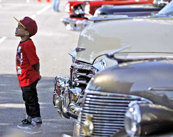 Jayden Steele, 4, of Highland Park, poses in front of a 1948 Chevy Deluxe Fleetline at the 19th Annual Cruise Night along Brand Blvd. in Glendale.