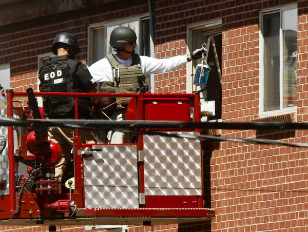 Bomb disposal experts lower an explosive device into James Holmes' apartment to destroy part of the booby traps found inside.