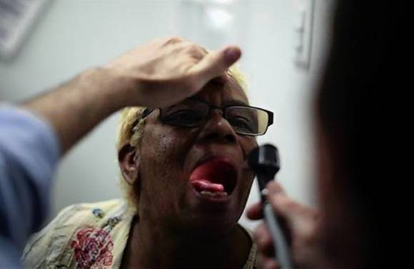 Rachel Lowe, 50, has her throat examined as part of a street medicine program between Venice Family Clinic and St Joseph Homeless Day Center in Venice