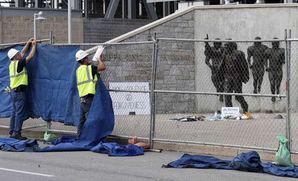 Workers put up tarps on a temporary fence around the statue of the late Penn State football coach Joe Paterno in preparation for removing the statue outside Beaver Stadium in State College, Pennsylvania, July 22, 2012. The removed statue was placed inside the stadium early Sunday, moments after the university president announced the school's intention to remove it.