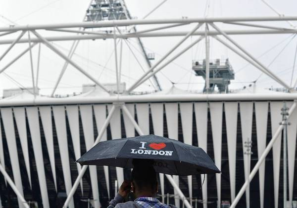 A worker outside the Olympic Stadium in Stratford uses an umbrella as protection from the rain in England last week.
