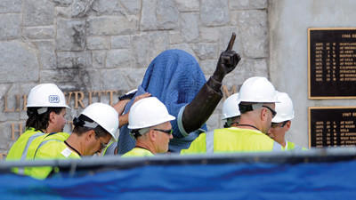 Penn State Office of Physical Plant workers cover the statue of former football coach Joe Paterno near Beaver Stadium on Sunday.