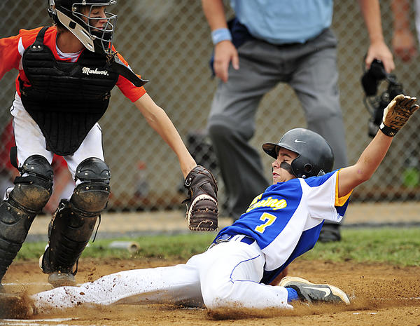 Clear Spring's Jaret Lazich (7) slides across home plate past Easton catcher Max Newnam during Sunday's Maryland 11-12 Little League state tournament game in Brunswick, Md.