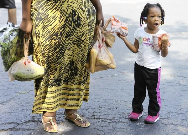 Harmony James, 3, and her grandmother carry away fresh food from Maywood's First Christian Church, which hosts a monthly giveaway.