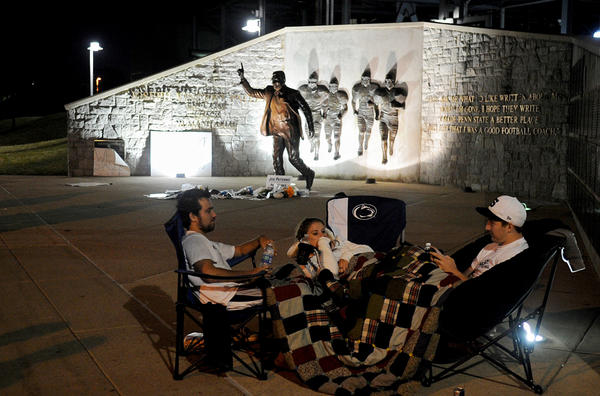 Penn State seniors Kevin Berkon, Courtney Brenner and Mike Elliot sit by the Joe Paterno statue during the early hours of Sunday, July 22, 2012, in State College, Pennsylvania.