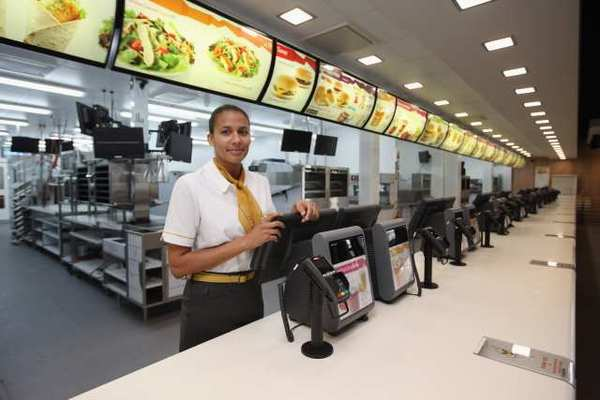Assistant manager Rachel Lucien stands at the checkouts in the world's largest McDonald's restaurant in the Olympic Park in London, England. The fast food chain suffered a rare profit slide in its second quarter.