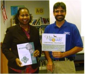 William Dandy Middle School Principal, Cassandra Robinson, receives a NatureScape Broward sign designating her school as one of 103 Broward County Public Schools achieving National Wildlife Federation Schoolyard Habitat certification.