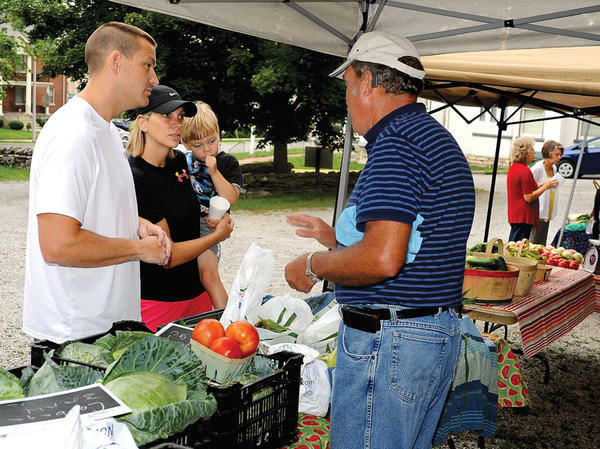 Mark and Kim Miller purchase corn and cucumbers Saturday from John Sparks of Rocky Knob Farm in Pilot View during the Winchester-Clark County Farmers Market.