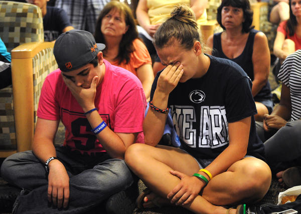 Penn State graduate Andrew Hanselman, left, and student Maddy Pryor react to hearing NCAA sanctions against the university including a fine as well as ban from bowl games and striking wins from the team's records due to the response of the university to the handling of the Jerry Sandusky child molestation charges.