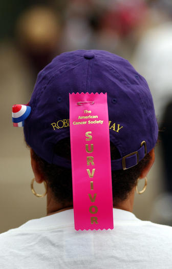 A ribbon indicates a breast cancer survivor  at an annual American Cancer Society 5K walk