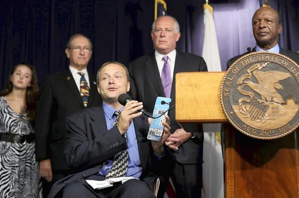 Bill Bogdan, disability liaison to the Illinois secretary of state, talks about new measures signed into law Monday by Gov. Pat Quinn, second from right. Secretary of State Jesse White, whose office targets illegal handicap parking, will enforce the laws, is at right.