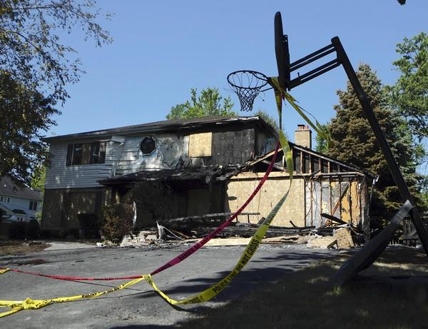Crime scene tape flutters from a basketball hoop Monday at the home in Lombard where Paula Rae Morgan died in what authorities are calling a suspicious fire.