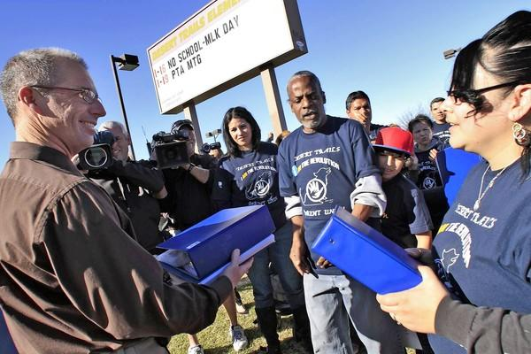 Desert Trails Elementary principal David Mobley receives signed petitions from parents in January. A judge has now ruled that the school board improperly allowed parents to rescind their support for turning the school into a charter.