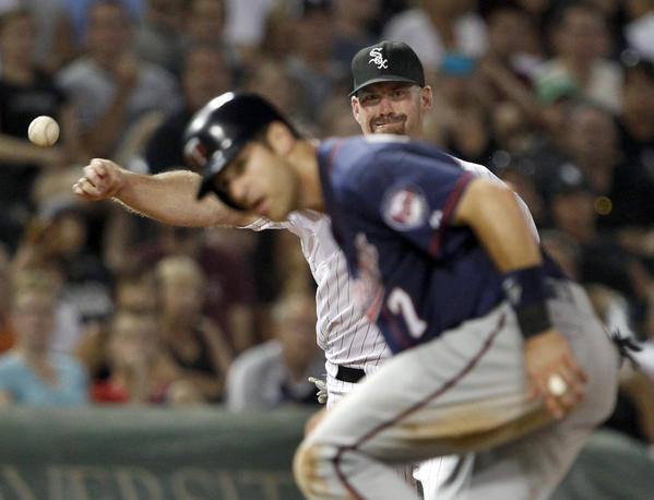 Twins baserunner Joe Mauer ducks as Sox third baseman Kevin Youkilis makes the throw.
