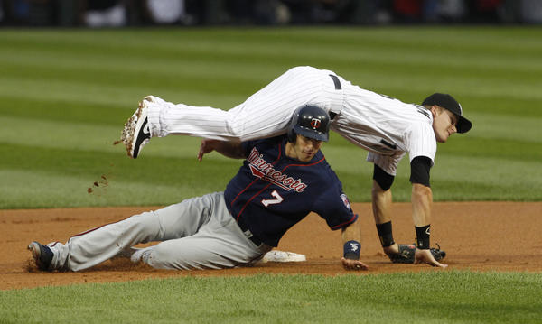 Sox second baseman Gordon Beckham lands on top of the Twin's Joe Mauer after making the relay throw.