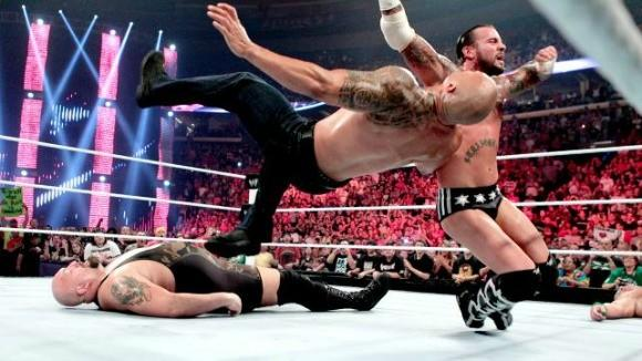 CM Punk delivers a clothesline to The Rock.