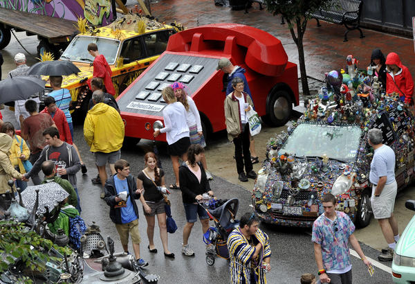 Crowds deal with the wet weather as they pass by Artcars parked along Charles Street for Artscape.