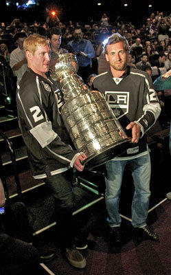 "Matt Greene and Jarret Stoll of the Kings carry the Stanley Cup into the ""Stanley Cup Champions 2012: Los Angeles Kings"" DVD premiere at Regal Cinemas in L.A. Live."