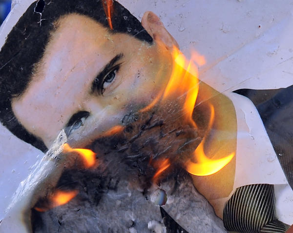 A picture taken on July 23, 2012 shows a portrait of Syrian President Bashar al-Assad burning during clashes between rebels and Syrian troops in the city center of Selehattin, near Aleppo.