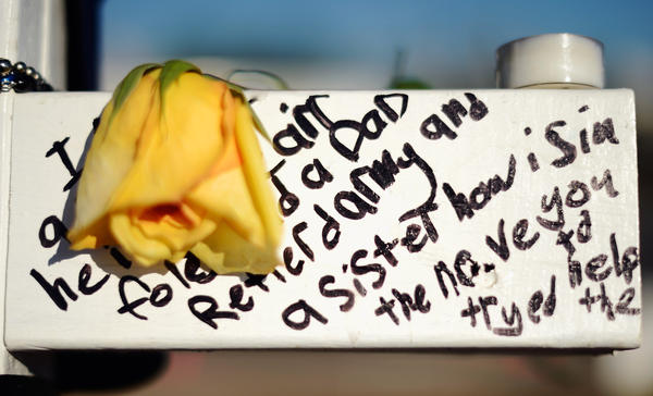 Writing is seen on a cross that stands at the makeshift memorial to the 12 movie theater shooting victims across the street from the Century 16 Theater July 24, 2012 in Aurora, Colorado.