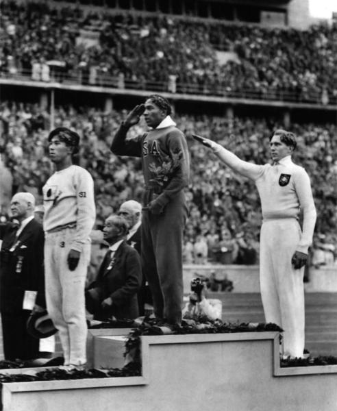 This 1936 file photo shows America's Jesse Owens, center, saluting during the presentation of his gold medal for the long jump, after defeating Nazi Germany's Lutz Long (right).