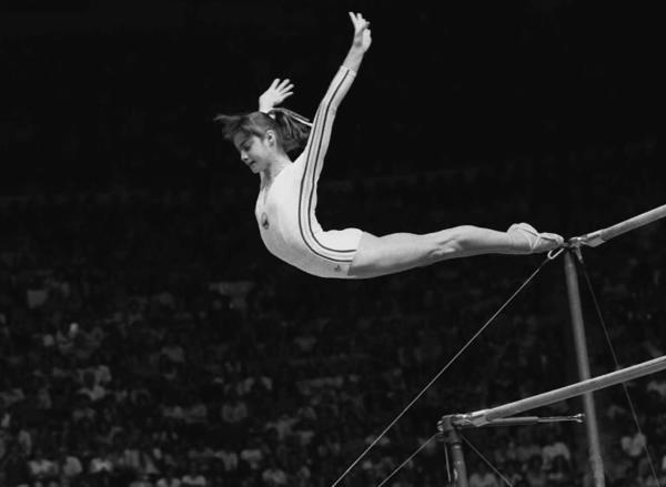 "Nadia Comaneci of Romania dismounts from the uneven parallel bars during a perfect ""10"" performance at the Summer Olympics in Montreal in 1976."