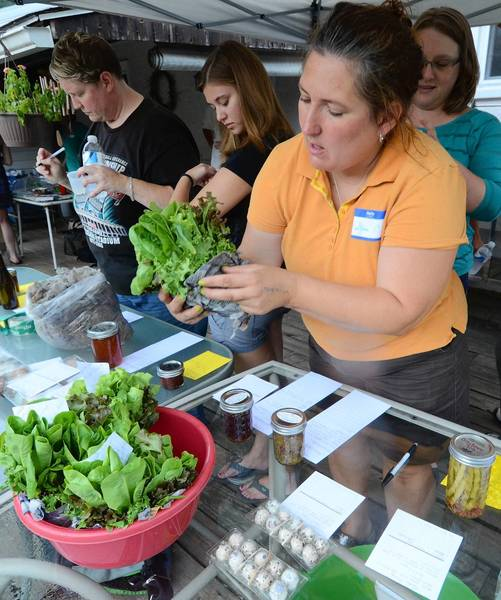 Stefani Campbell of Coopersburg views produce offerings during food swap in Springfield Township, Bucks County on Sunday, July 15, 2012.
