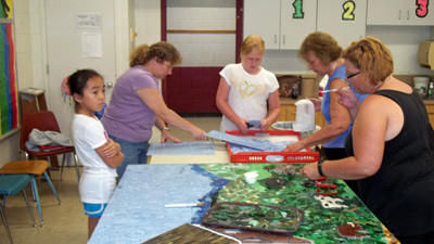 Student Hannah Slope, art teacher and project organizer Jane Holt, Hadyn Phillippi, Shirley Sowerbrower and Heather Houghton lend a hand to complete Rockwood elementary's new 30-by-8-foot glass mosaic that will be installed near the school's gym within the next few weeks.