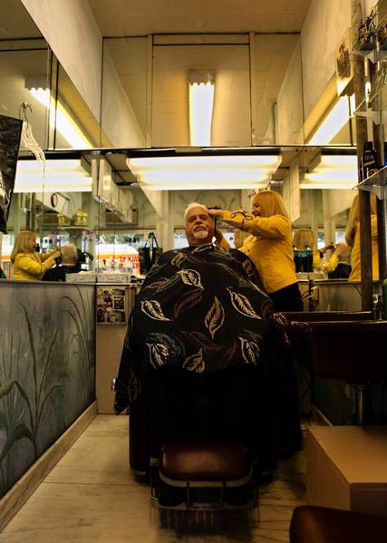 Jan Bruno cuts Carlos Gaivar's hair at her tiny one-chair shop at Hollywood Boulevard and Vine Street in Hollywood. Bruno has owned the shop for 23 years; the building's new owners have told her she must leave.