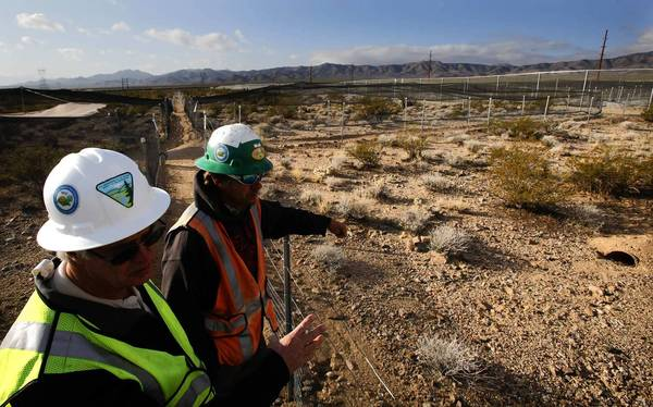 Bureau of Land Management biologist Larry LaPre, left, and George E. Keyes Jr. of BrightSource check on the tortoise population in pens at the site where the company is building a solar energy facility in the Ivanpah Valley on the California-Nevada border. No more such developments will be allowed in the valley.