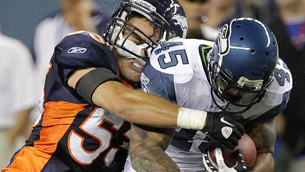 Denver Broncos linebacker Mike Mohamed (left) tackles Seattle Seahawks running back Thomas Clayton in the fourth quarter of a preseason NFL football game Aug. 27 in Denver.