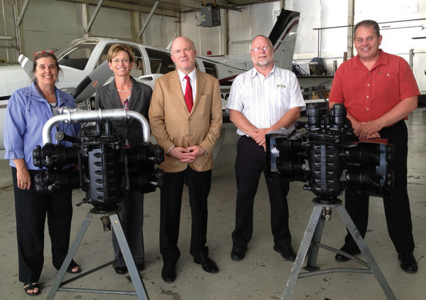 "Standing with two general-aviation aircraft engines that recently were donated to the Hagerstown campus of the Pittsburgh Institute of Aeronautics are, from left, Katrina Bradshaw, executive director of Build A Plane; Lauretta Godbey, vice president of marketing for Avemco Insurance Co.; Jonathan ""JJ"" Greenway, president of Avemco; Thomas O'Keefe, director of Pittsburgh Institute of Aeronautics in Hagerstown; and Tracey Potter, president of Hagerstown Aircraft Services Inc."