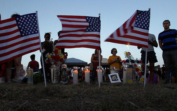 A public showing of patriotism and faith as mourners gather during a public service across the street from the movie theater in Aurora, Colo.