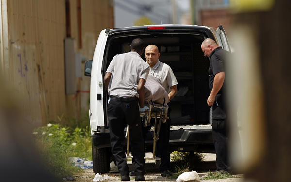 Police remove a body from a vacant lot in the 1800 block of West Walnut Street in Chicago.