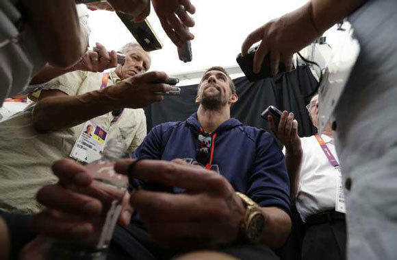 Michael Phelps is surrounded by reporters during a pre-Olympics news conference in London.