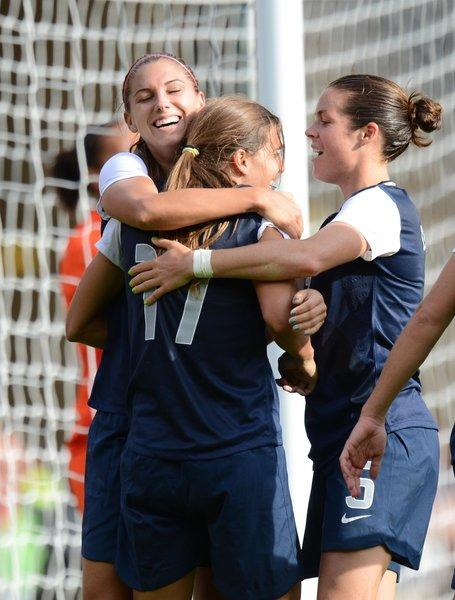 USA forward Alex Morgan (13) hugs midfielder Tobin Heath (17) after scoring a goal against France during the preliminary match before the London 2012 Olypmic Games at Hampden Park. USA won the match 4-2.