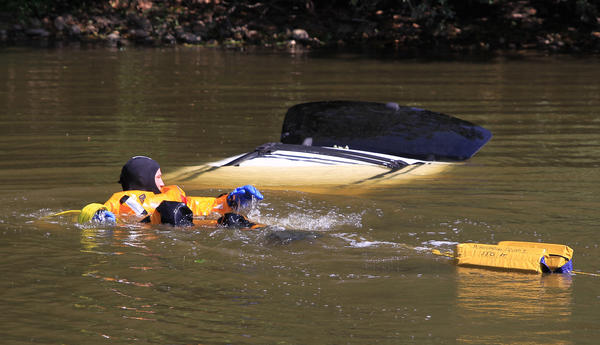 Emergency divers search a car in the water, near 2500 Brush Rd., in Schaumburg, Illinois.