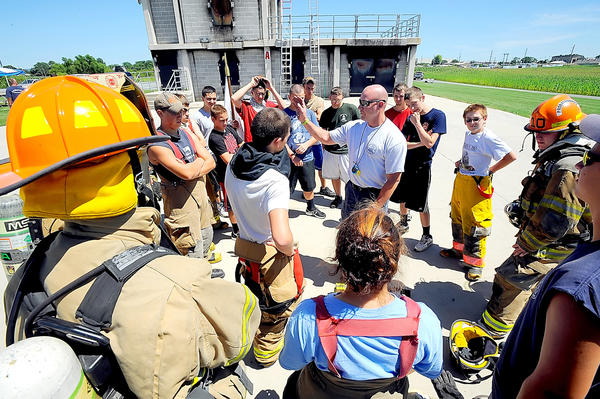 Clyde Thomas, center with sunglasses, works Wednesday with junior firefighters during a training camp near Chambersburg, Pa. Thomas is training coordinator and lead instructor for Franklin County's Public Safety Training Center.