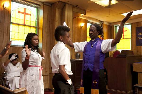 "Kimberly Herbert-Gregory as Sister Sweet (seated, in background), Toni Lysaith as Chazz Morningstar, Jules Brown as Flik Royale, and Clarke Peters as Bishop Enoch Rouse in ""Red Hook Summer."""
