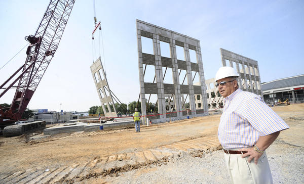 Owner Asad Ghattas watches as workers get ready to secure a 54-foot tilt panel as part of the new office building under construction at Fountainhead Plaza in Hagerstown.