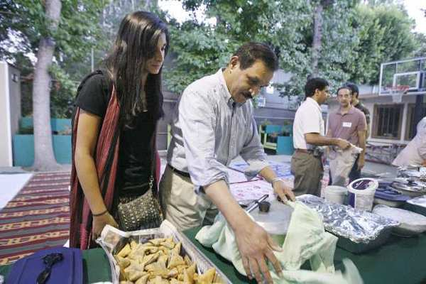 The Islamic Congregation of La Canada Flintridge will hold its annual interfaith Ramadan potluck dinner on Friday. Above, Husnain Shahzad, center, and his daughter, Noor, 13, bring rice and fruit salad to the 2011 event.