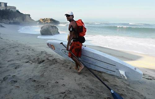James Pribram says bon voyage as he hauls his stand-up paddleboard and gear at Pearl Street beach, where he embarks on a paddle journey along the Southern California coast to the Mexican border in an effort to bring awarness to rivermouth pollution.