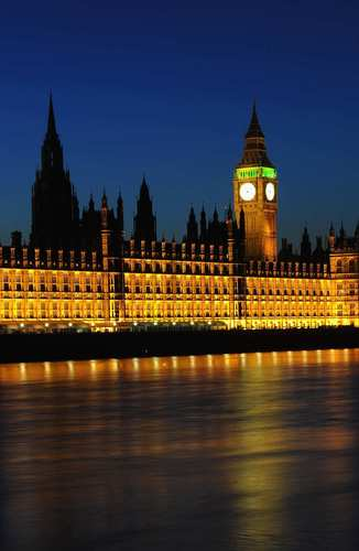 Lights burn bright around dusk at the Houses of Parliament, officially known as the Palace of Westminster, in London.