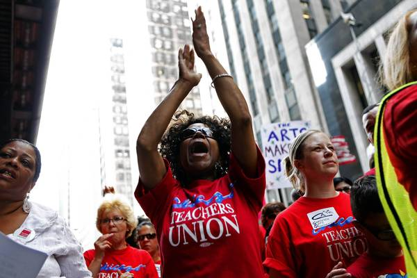 Teachers listen to speakers at a rally Wednesday outside Chicago Public Schools headquarters. The teachers are seeking more money for neighborhood schools, teacher salaries, and art, music and physical education programs.