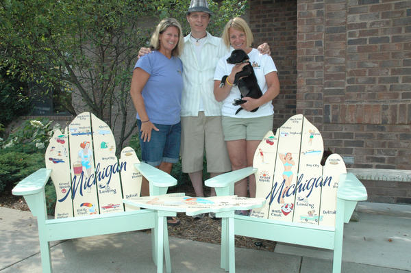 Little Traverse Bay Humane Society executive director Deter Racine (from left), artist Aaron Kirby and director of marketing and development Marci Singer stand with the chairs and table up for raffle at the humane society's Howl at the Moon fundraiser.