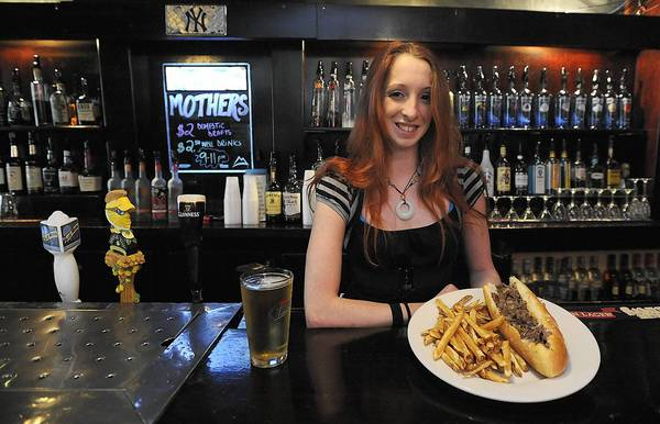 Kristin Palese, a bartender at Mother's Bar and Grille in Easton, holds a cheesesteak and french fries platter.