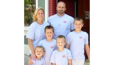 Ambre (back row, from left) and Earl Flynn, the new owners of Mighty Fine Pizza, stand outside the downtown Petoskey shop with their children (front row, from left) Lilian, Garrett, Riley and Bradley.