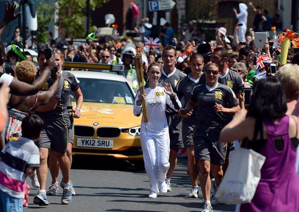 People pack the streets as torchbearer Zoe Jones carries the Olympic flame during the London torch relay in the streets of Peckham in south London.